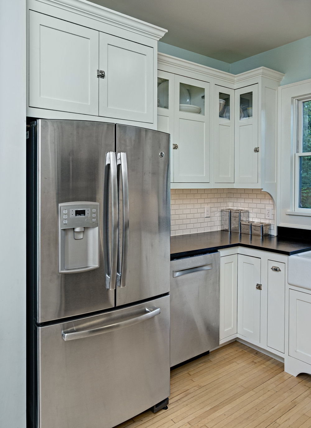 A new layout, custom white Shaker-style cabinets and black PaperStone counters blended new with old seamlessly.