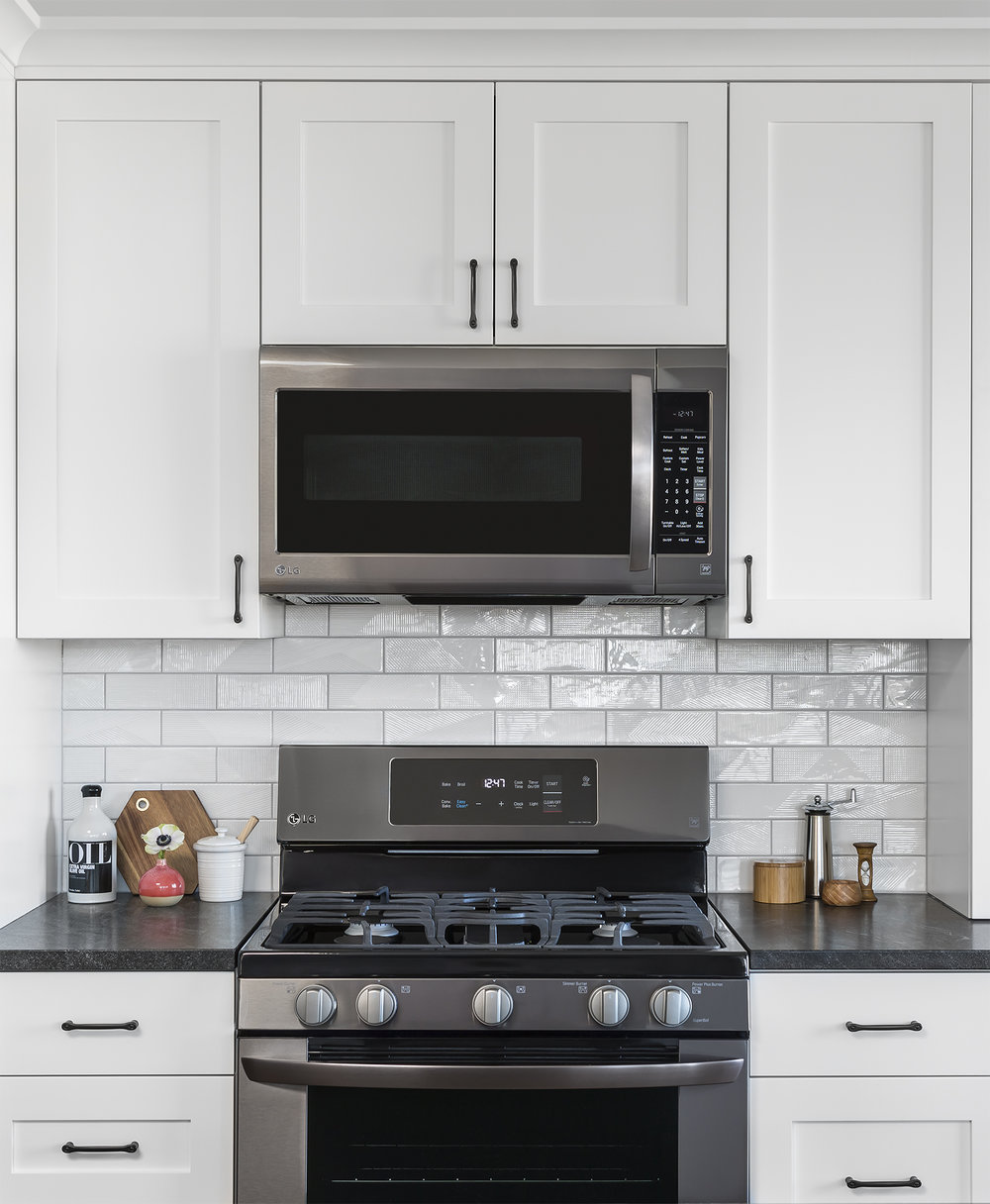 Clean-lined cabinetry and a geometric backsplash tile suit the modern aesthetic of the homeowners.