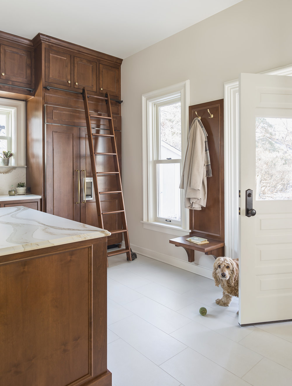 A small bench and hooks near the back door keeps things tidy. Tiled floors with in-floor heat make feet (and four-legged friends) happy!