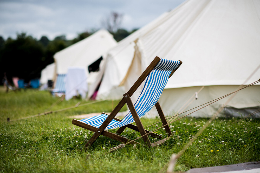 DELUXE BELL - The classic and beautiful canvas Deluxe Bell Tent offers both comfort and style. A fully carpeted space with a doormat, mirror, side table and LED lights. Both sizes come with bed linen and 13 tog duvets.