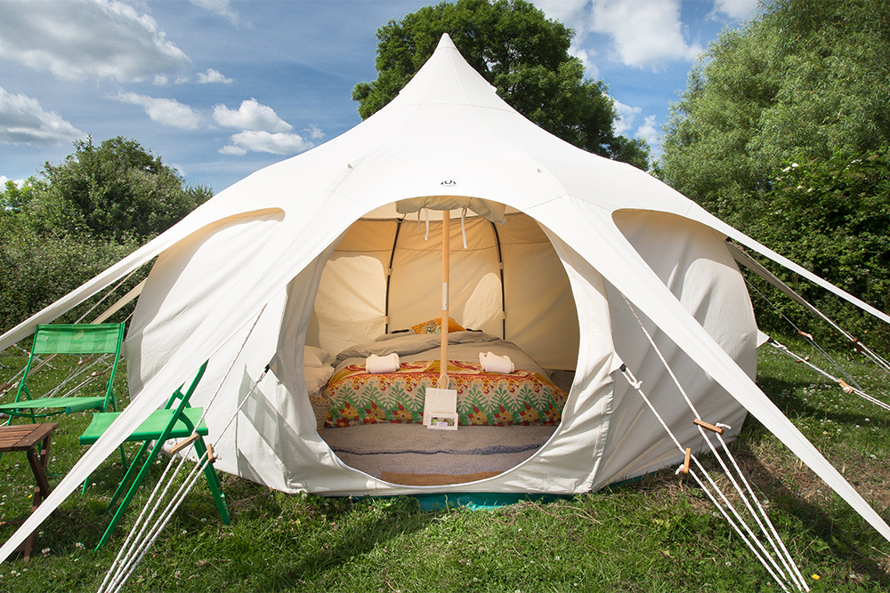 LOTUS BELL - The charming and unique design of the Lotus Bell Tent offers something a little bit different with a Kingsize bed, a luxury memory foam mattress and memory foam topper, bed linen, 13 tog duvets and cosy throws. Also includes LED lights, hanging rail and hangers, a table and chairs, welly basket, storage box, doormat and rug.