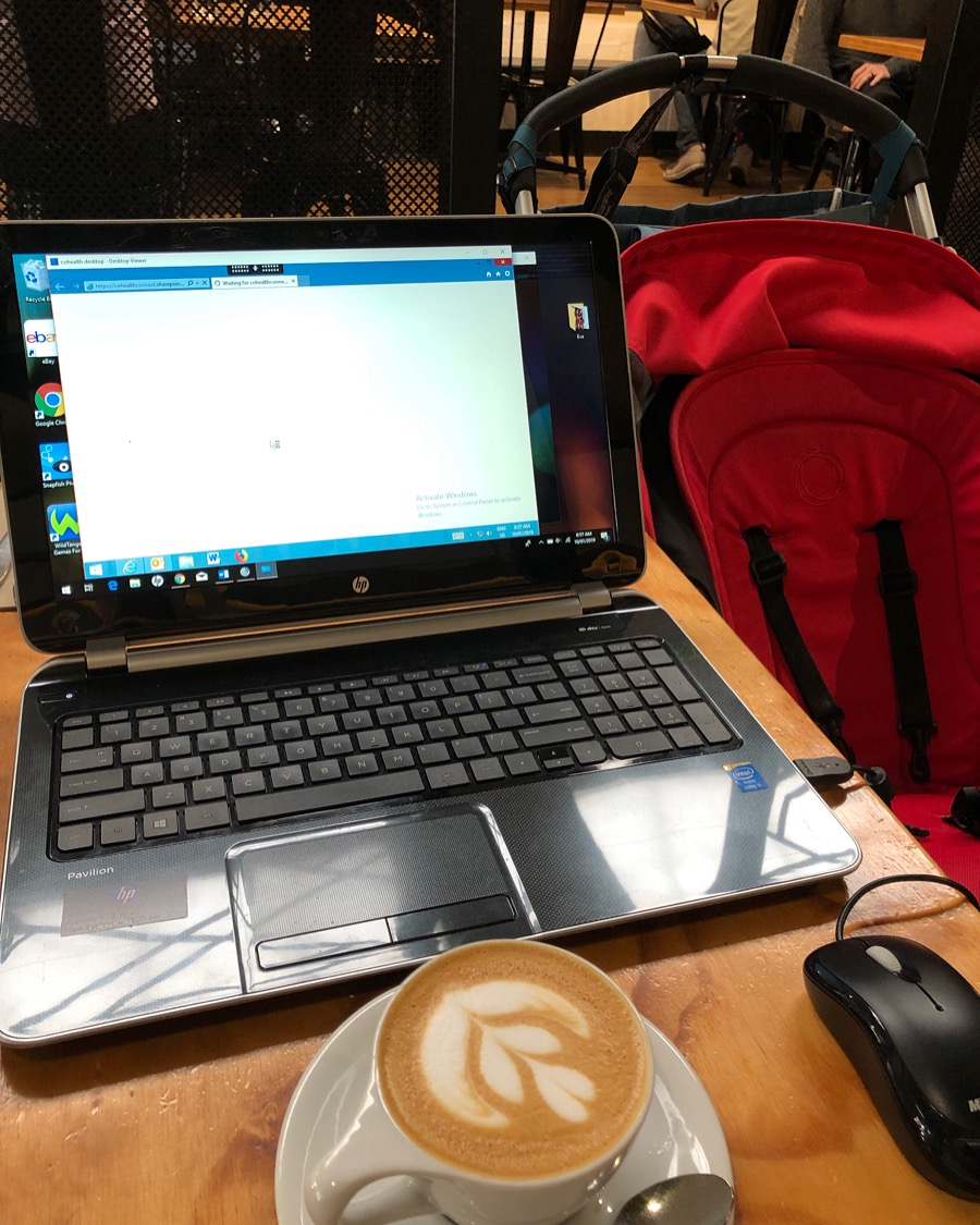 Working in cafe on laptop with coffee and baby