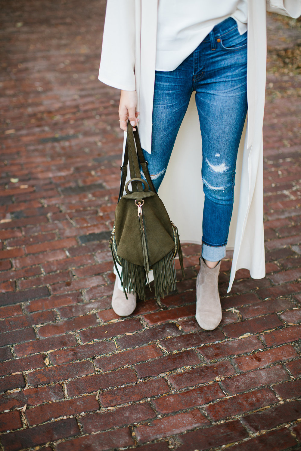 Julia Friedman wearing a Nude Duster Coat Rebecca Minkoff Backpack with Madewell Jeans and Steve Madden Suede Booties
