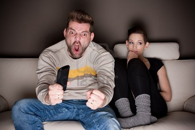 9687914-goaaaaal-a-man-watching-football-while-his-girlfriend-is-sitting-besides-him-bored-showing-the-diffe.jpg