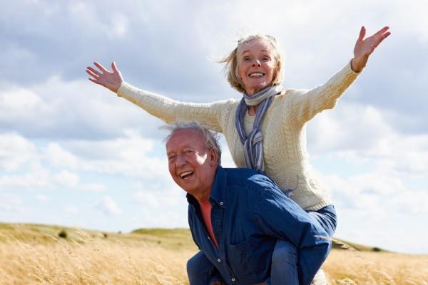 Senior Man Carrying Senior Woman On Walk In Countryside