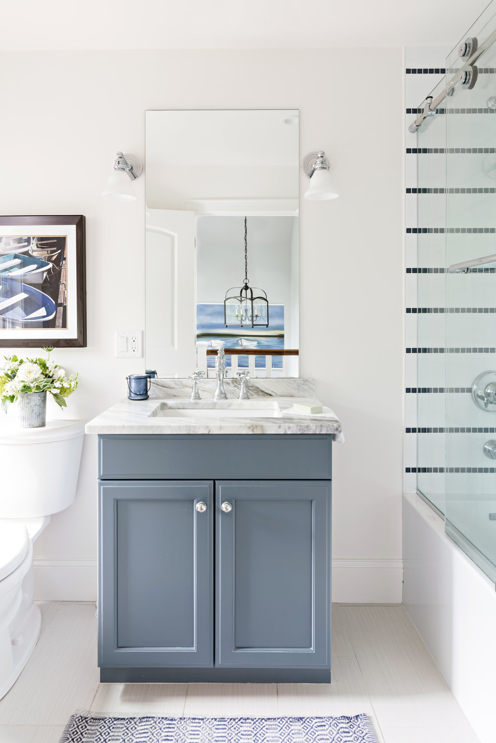 Beachy porcelain tiles. Calacatta Bluette vanity top and a shower wall detail that gives this New England home is nautical flair.