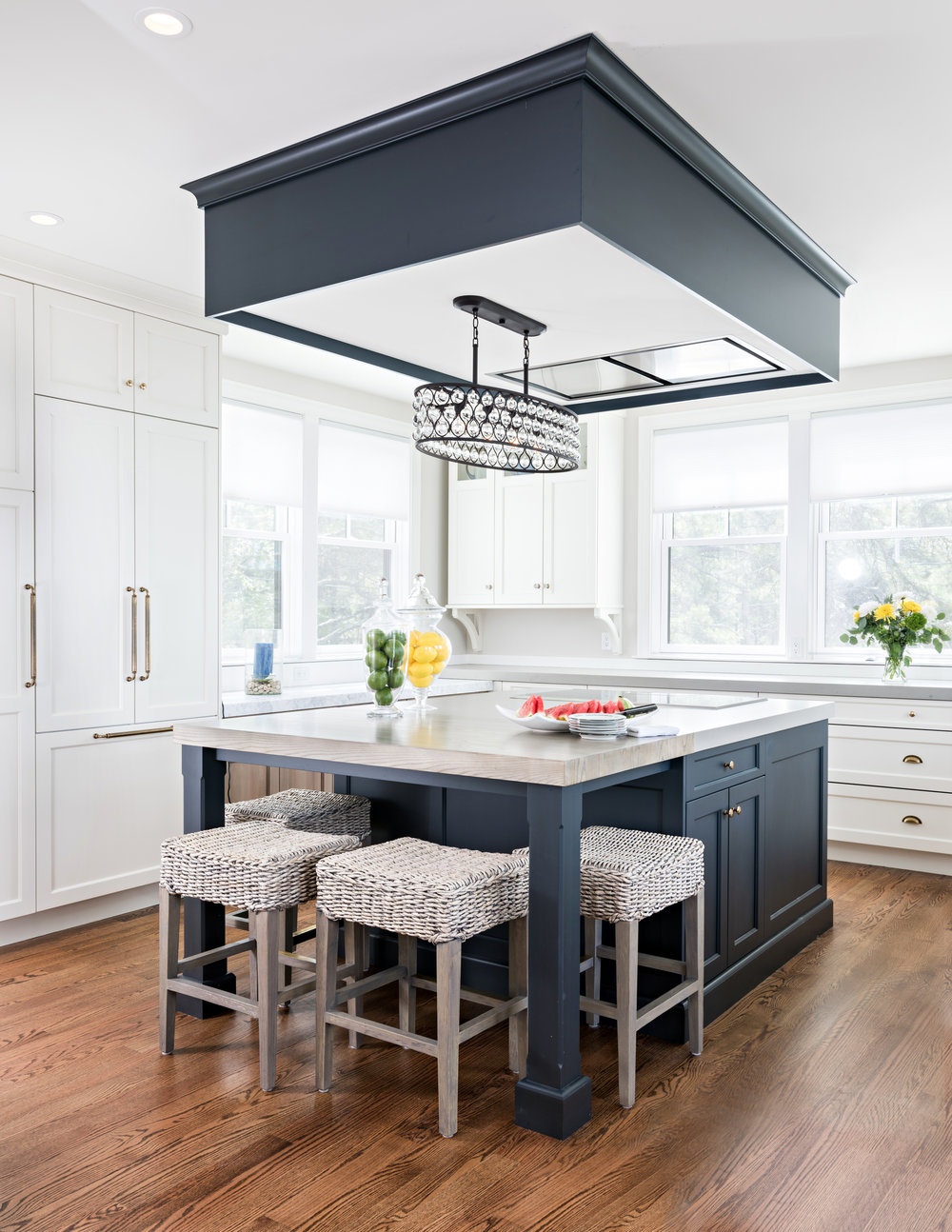 Coastal doesn't have to be void of sparkle! High above the navy island hangs the jewelry, visually connecting the soffit and the surface below. Mixed metal finishes invite a casual elegance and real life spaces.