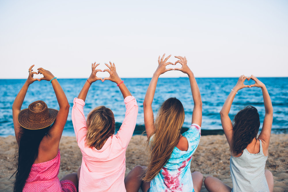 Girls in colorful clothes holding up a heart sign while they get a sun tan on Lake Michigan in Chicago.