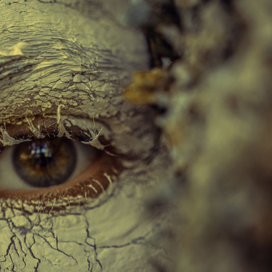 [image] An eye peers from a face covered in clay, resembling bark. A blurry tree in foreground.