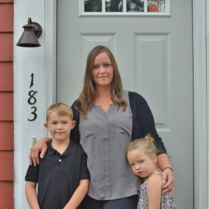 Homeowner Jess with her kids, Drew and Jillian, in front of their new home.