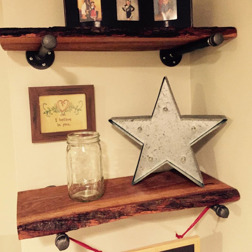 These DIY shelves echo the pipes from the bar table and bring in great natural texture with the raw edge of the wood.