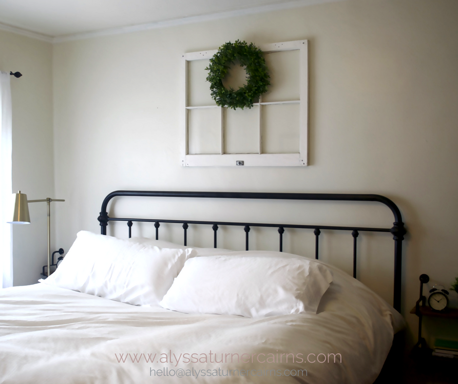 This great bed frame is the foundational piece in this farmhouse inspired bedroom design. The window and wreath are such a sweet touch!