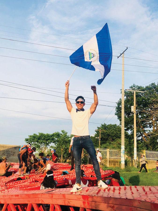 """Mel Prado, 32 años, enarbola una bandera sobre un árbol de hierro conocidos como chayopalos en referencia a la vicepresidenta de Nicaragua conocida como Chayo y quien instalo los """"arboles"""" en la capital. (Foto tomada de redes sociales)"""