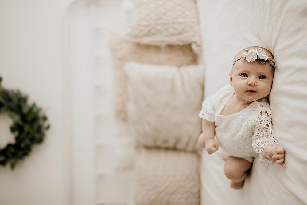 Beautiful Newborn Baby Girl in Flower Headband Lying on the Bed