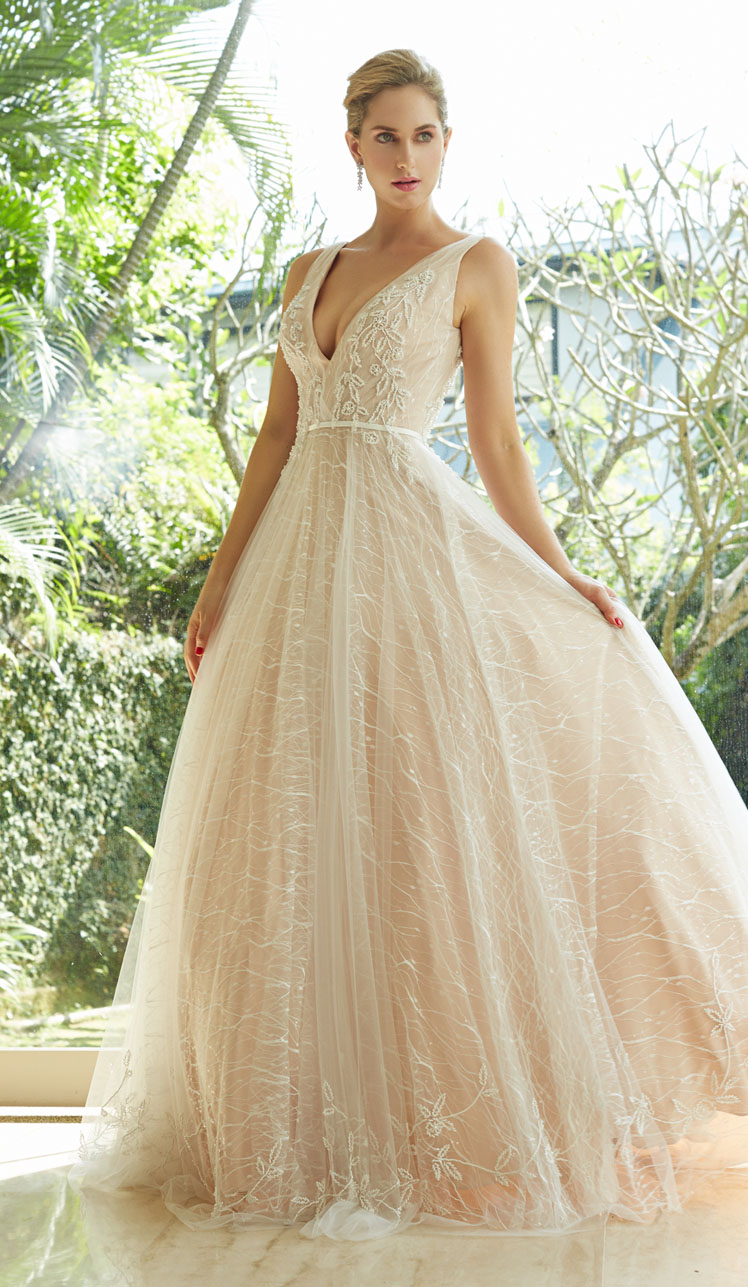THE SUNRISE - Exude radiance and grace in this lustrous dress. A fitted bodice, accentuating the natural waist, flairs into an abundant flowing skirt. The skirt's four beautiful blush layers are finished with pure handcrafted beading, for a profound and mesmerizing design.