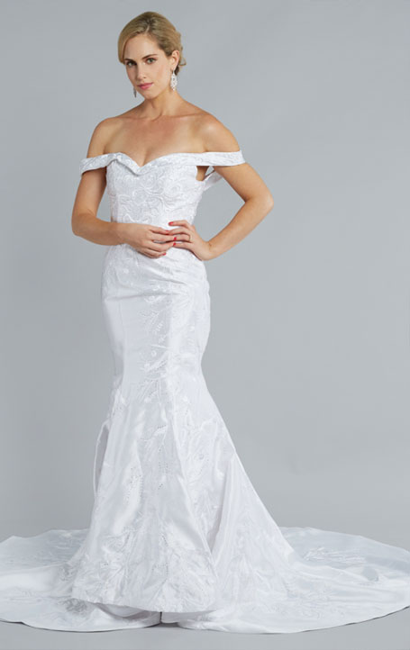 THE LILY - Brilliant Swarovski crystals embellish this incredibly flattering mermaid gown. Three layers of elegant satin fall gracefully from the sweetheart shape and down to the sweeping train. Sleeves fall off-shoulder to create a subtle allure to balance the soft neckline and delicately cinched waist. The Lily is pure poise.
