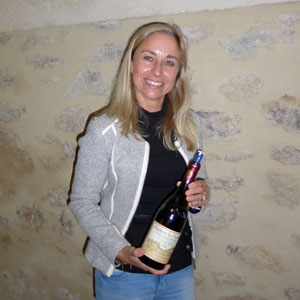 Sylvie Chabran poses with a Bottle of cadettes at Chateau La Nerthe