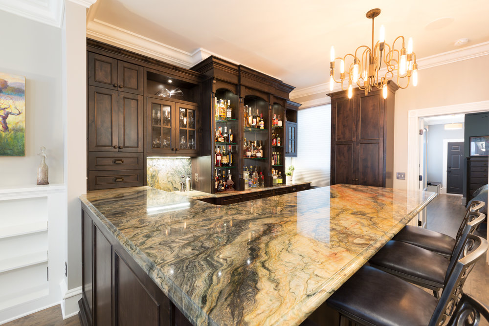 Remodeled Loft Bar with dark wood cabinets and stone counter tops.