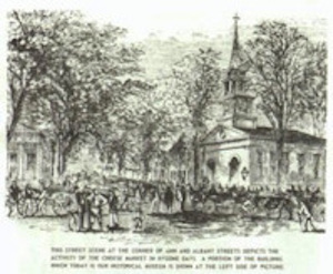 An old print showing the street scene at the corner of Ann and Albany Streets in Little Falls, depicting the activities of the Cheese Market in bygone days. A portion of the building which today is the Little Falls Historical Society is visible at the left side of the picture.