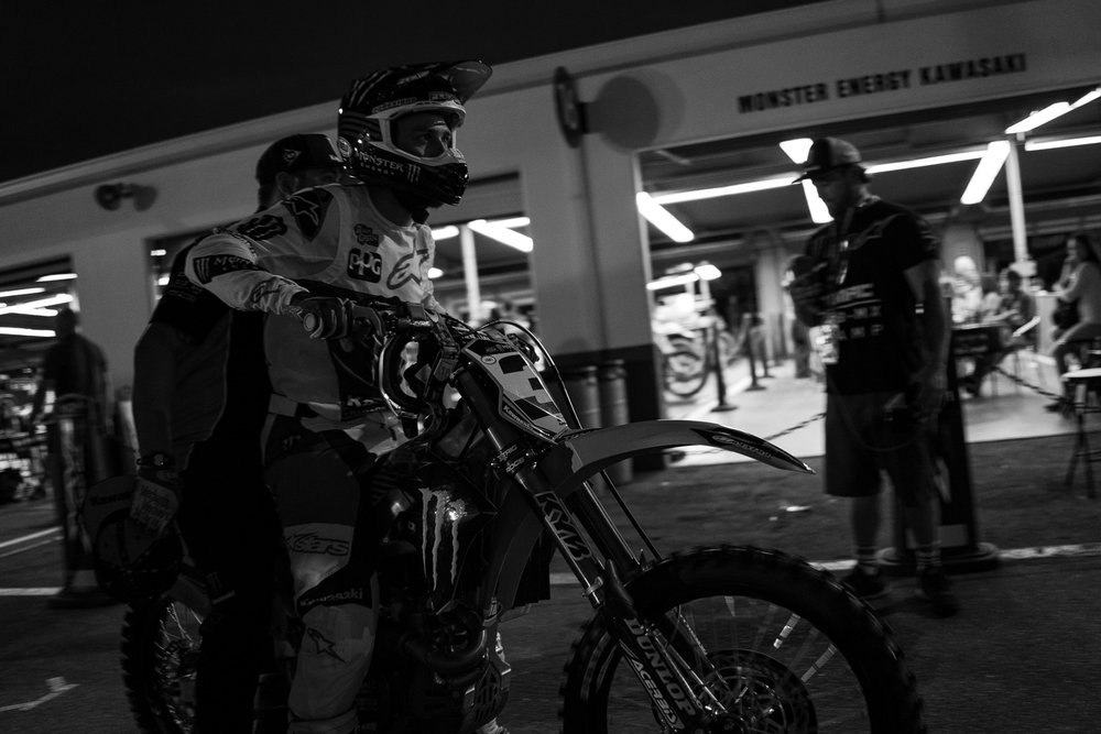 The paddock in Daytona makes for unique photos, like this shot of Brian Kranz and Eli Tomac on their way to the track while the auto racing garages shine light in the background.