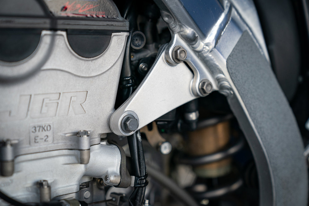 In Atlanta we noticed the intricately crafted engine hangers on the JGRMX/Yoshimura/Suzuki Factory Racing RM-Z450 bikes had been replaced with bigger, triangle style pieces. We incorrectly assumed a bigger part meant a more rigid feeling of the chassis, but Brad Bensch informed us that the new parts are actually thinner and as a result, make the chassis softer.
