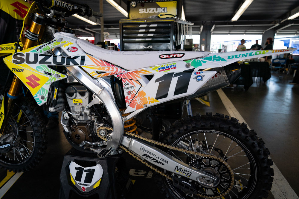 """The H.E.P. Motorsports Suzuki team has mixed up the look of their RM-Z450s in recent weeks and the trip to Florida meant graphics with brightly colored flowers and a white GUTS Racing seat cover. As much as this worked in Daytona, it would have worked just as well in Detroit as a nod to Jackie Moon and the Flint Tropics basketball team of """"Semi-Pro"""" fame. Let's get tropical!"""