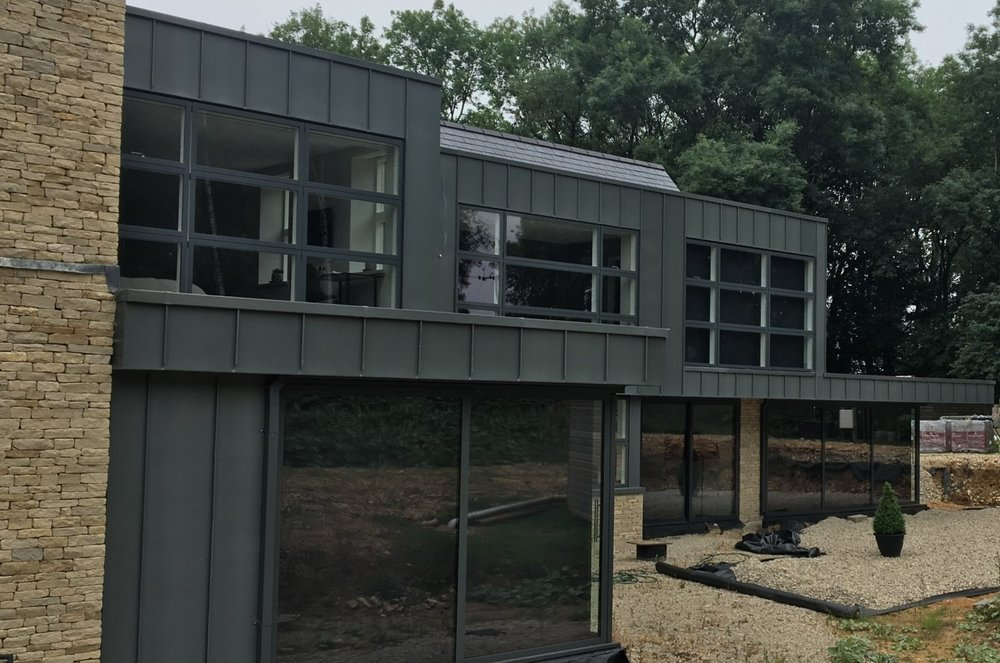 CHIPPING CAMDEN - The darker pre weathered Graphite-grey Rheinzink was used in this new build project. The large private house uses the zinc cladding along with large sections of glazing to give an urban feel against the contrasting stonework.