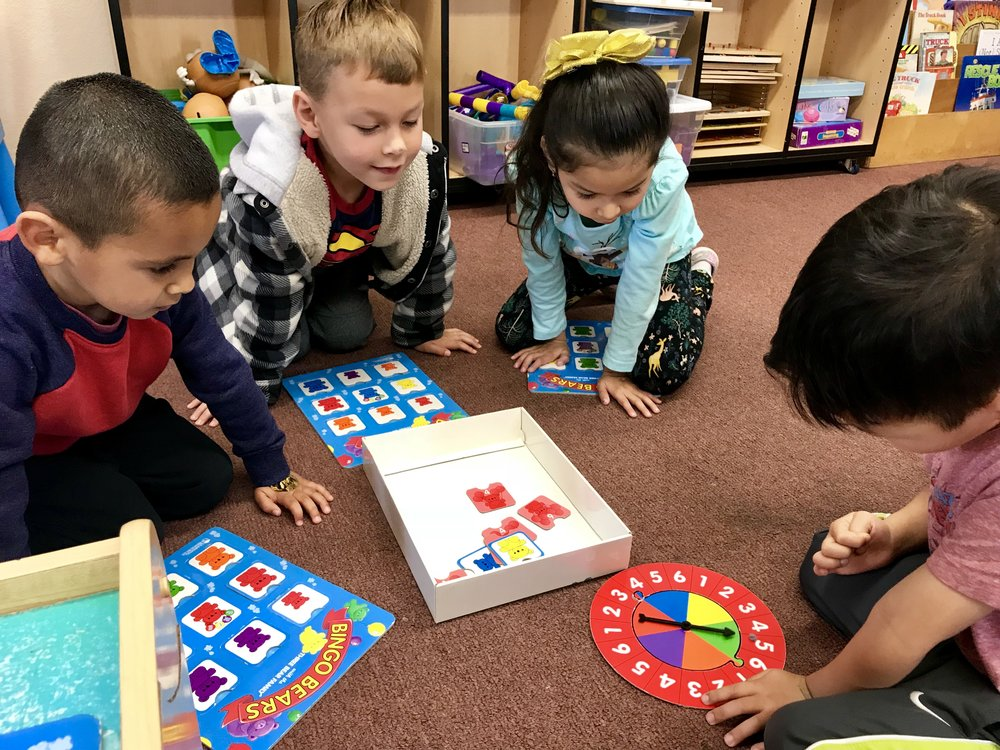 Sharing toys, playing cooperatively, and taking turns in small groups.