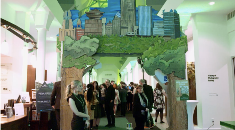 Upcycled cardboard art (6 total environmental and Rochester themed arches) from Rochester's own Magnus Apollo Design were on display at the Fast Forward Film Festival Green-Carpet Gala in 2018 held annually at the George Eastman Museum. This event features zero/minimal waste kiosks from Impact Earth and helps teach guests composting, recycling, and landfill education.