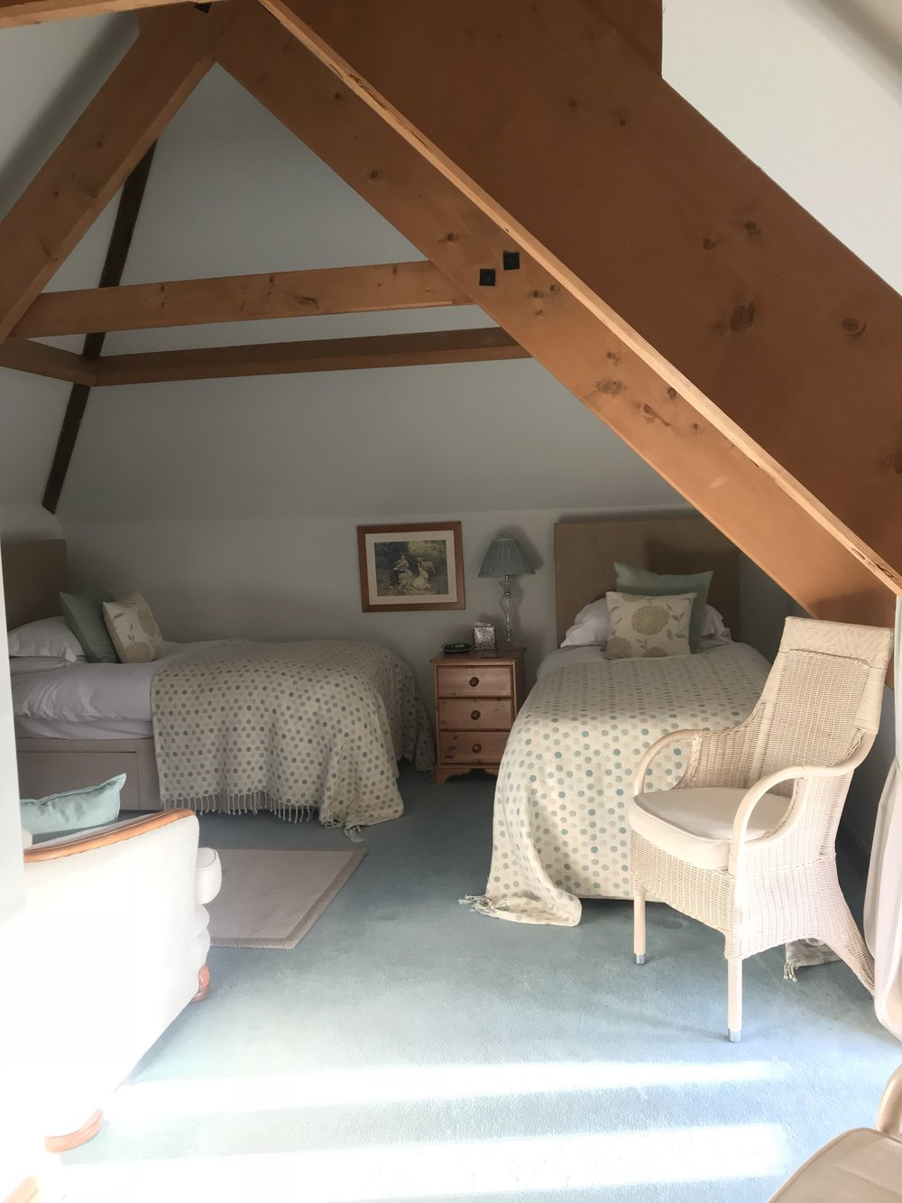 Cow Shippon Twin - The Cow Shippon twin room is cosy, yet spacious with wonderful beams, a sofa to relax on, an ensuite bathroom with a bath and shower over. The room, formerly a hay loft comes complete with a beverage tray, homemade biscuits and fresh flowers from the garden.