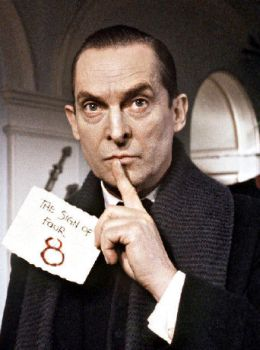 A medium shot of actor Jeremy Brett as Sherlock Holmes, with a mysterious paper in one hand and his index finger pressed against contemplative lips.