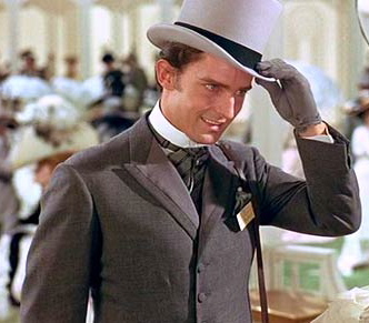 Actor Jeremy Brett in a lighter grey formal suit with matching gloves tips a dove-grey top hat in the Ascot scene from the movie My Fair Lady.