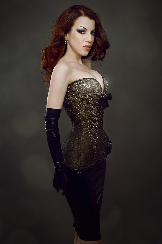 A woman with pale skin and red hair wears long black gloves and a sparkly, curvy corset in dark gold peacock colors.