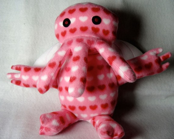 A pink three-tentacled squid-god plushie with tiny red and white hearts and adorably round black eyes.