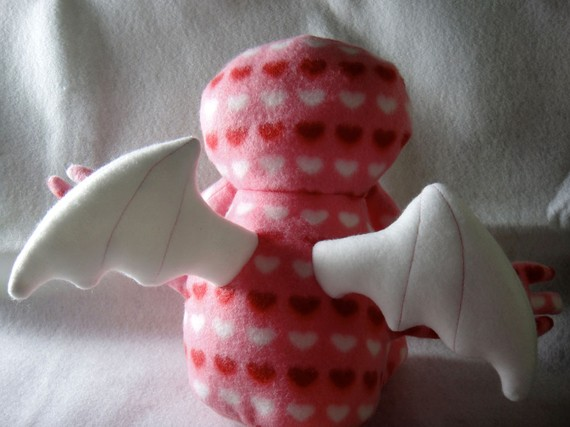 The same pink, white, and red squid-god plushie, back view, showing cuddly white plush wings.