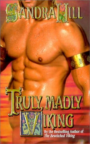 The very idealized torso of a very naked man, wearing only a wide gold armband around his bicep, standing in front of a venomously pink sunset. The text tells you this is the cover for Truly, Madly Viking, by Sandra Hill.