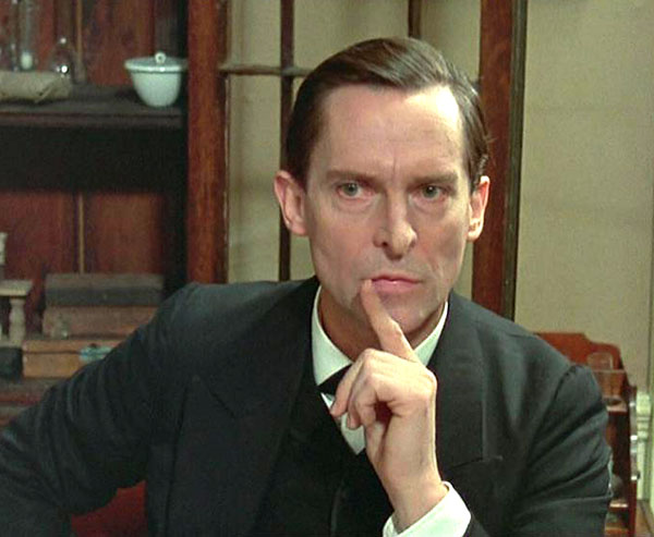 Actor Jeremy Brett, a man with pale skin and dark hair, wears a charcoal Victorian suit and holds one finger to his lips in a gesture indicating rapid thought.