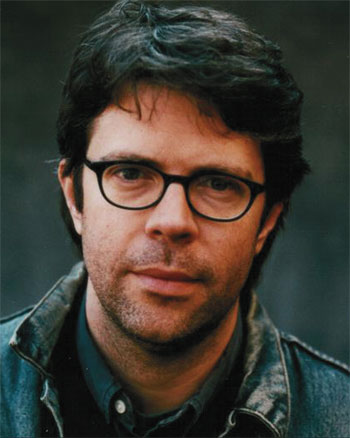 A white male author with shaggy hair in dark glasses.