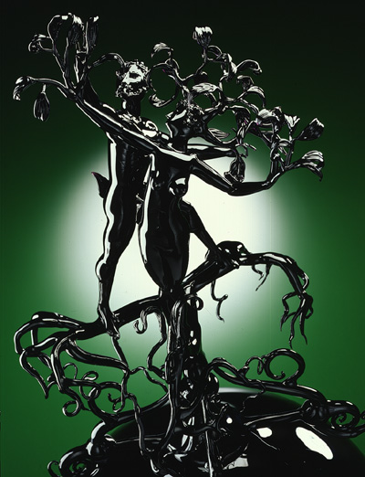 A black glass figure of a woman, Daphne, whose arms are becoming branches, hair leaves, and legs the roots of a tree. The black glass figure of Apollo attempts to embrace her as she transforms.