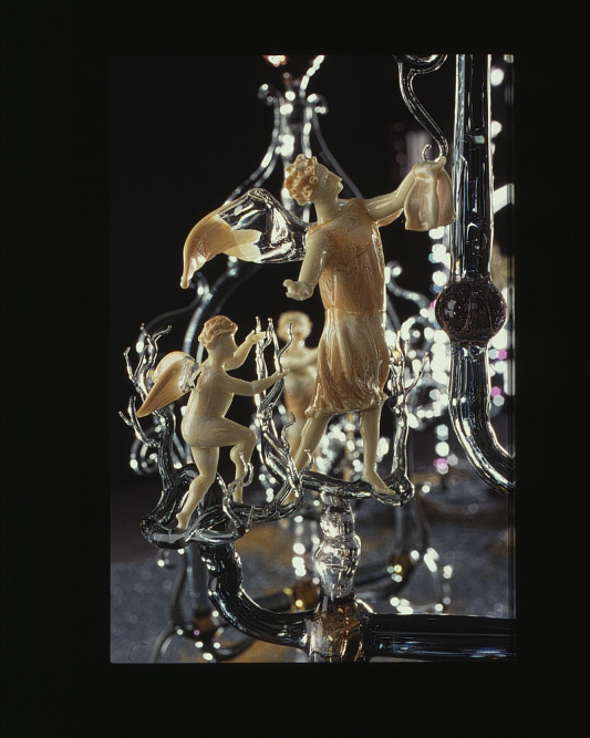 Cream glass winged figures with clear glass supports.