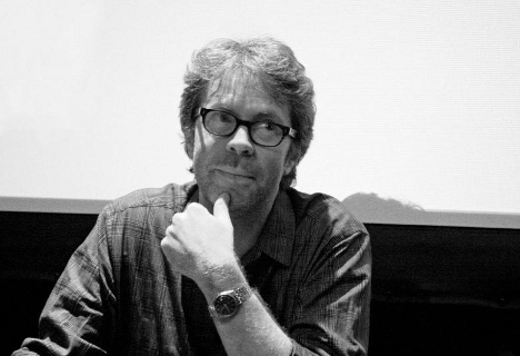 A white male author with shaggy hair in black glasses.