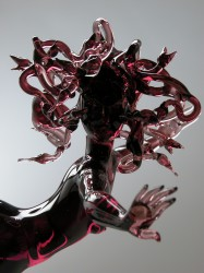 A dark purple glass woman with hand outstretched, and sinuous purple glass snakes for hair.
