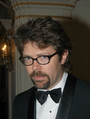 A white male author with shaggy hair and a beard in black glasses.