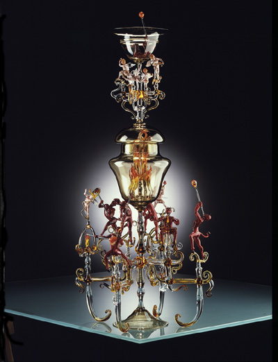 A goblet surrounded and supported by the figures of cream-glass angels and red-glass devils.