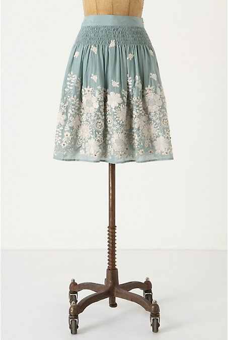 A mid-length circle skirt in robin's egg blue with swirling floral embroidery in heavy white thread. Tiny beads of pale golden wood appear here and there as accents.