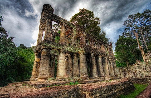 A ruined set of columns yielding to greenery and decay stretches toward a foreboding dark blue sky.