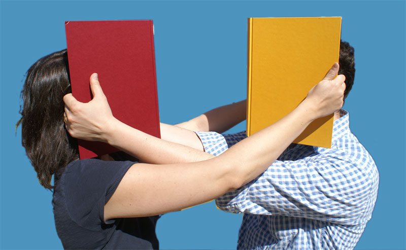 Two people, a white man and a white woman, each holding an open book smashed up against each other's face, so that they cannot see anything else including each other.