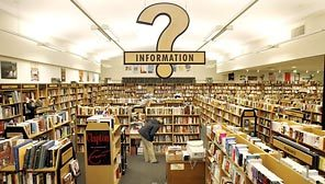 A giant question mark sign labeled INFORMATION hangs over a wide space full of shalves and books.