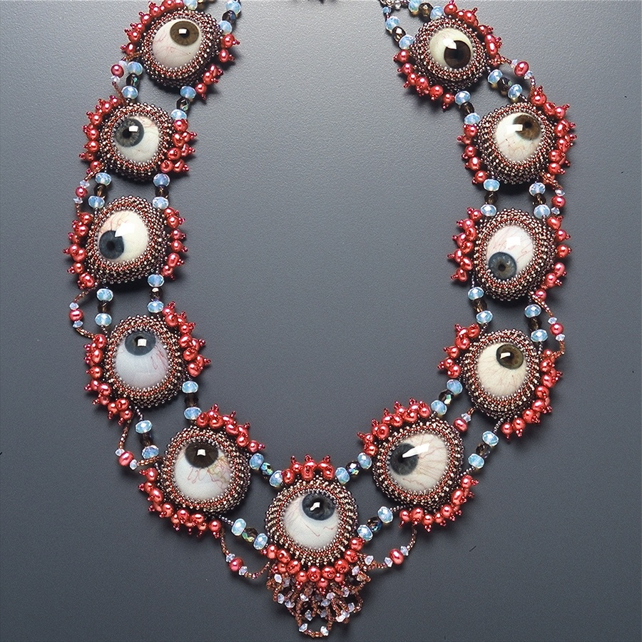 Glass eyeballs wheel in various directions, strung together in a wide necklace with red and turquoise seed beads.