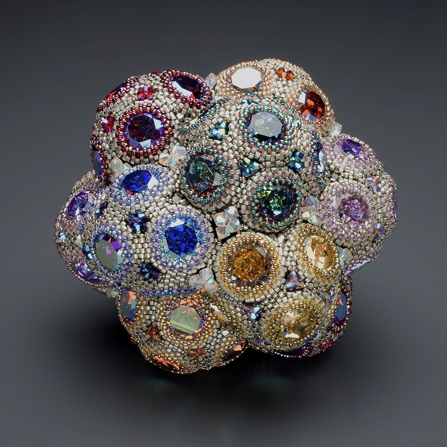 Swarovski crystals of many sizes and colors, assembled into bubble-shaped units. Those bubbles have then been put together to make something that looks like a sparklier version of a Wonka gobstopper.